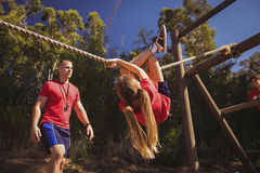 Trainer assisting a girl in obstacle course training Royalty Free Stock Photo