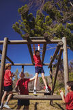 Trainer assisting girl to climb monkey bars during obstacle course training Royalty Free Stock Photo