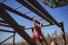 Trainer assisting girl to climb monkey bars during obstacle course training Stock Photography