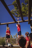 Trainer assisting girl to climb monkey bars during obstacle course training Royalty Free Stock Images