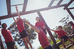Trainer assisting kids to climb monkey bars during obstacle course training. At boot camp Stock Photo