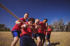 Trainer assisting kids in tug of war during obstacle course training. In the boot camp Royalty Free Stock Image