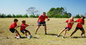 Trainer assisting kids in tug of war during obstacle course training stock video