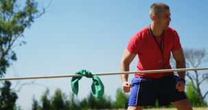Trainer assisting kids in tug of war during obstacle course training stock footage