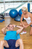 Trainer assisting man with abdominal crunches at fitness studio. Smiling female trainer assisting young men with abdominal crunches at fitness studio Royalty Free Stock Images