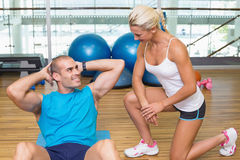 Trainer assisting man with abdominal crunches at fitness studio. Smiling female trainer assisting young men with abdominal crunches at fitness studio Stock Photo