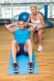 Trainer assisting man with abdominal crunches at fitness studio Stock Photos