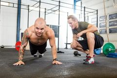 Trainer Assisting Man In Doing Pushups Royalty Free Stock Photo