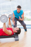 Trainer assisting man with dumbbells. Trainer assisting men with dumbbells in fitness studio Stock Images
