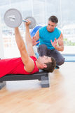 Trainer assisting man with dumbbells. Trainer assisting men with dumbbells in fitness studio Royalty Free Stock Photography