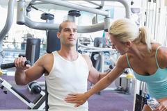 Trainer assisting man on fitness machine at gym. Female trainer assisting men on fitness machine at the gym Royalty Free Stock Photos
