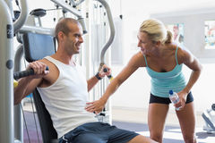 Trainer assisting man on fitness machine at gym Stock Photos