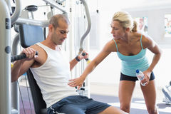 Trainer assisting man on fitness machine at gym. Female trainer assisting men on fitness machine at the gym Royalty Free Stock Photo