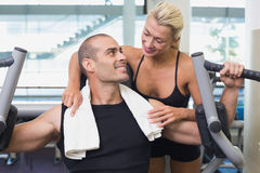 Trainer assisting man on fitness machine at gym Stock Images