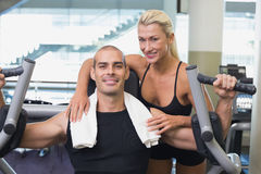 Trainer assisting man on fitness machine at gym Royalty Free Stock Images