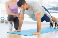 Trainer assisting man with push ups. Female trainer assisting men with push ups at gym Royalty Free Stock Photo