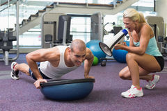 Trainer assisting man with push ups at gym Stock Photos