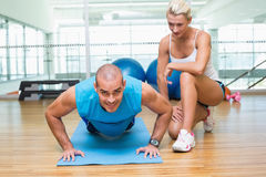 Trainer assisting man with push ups at gym. View of a female trainer assisting men with push ups at the gym Royalty Free Stock Images