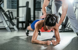 Trainer assisting a muscular woman on a plank position. Royalty Free Stock Image