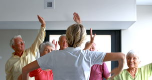 Trainer assisting senior citizens in exercising stock footage