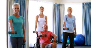 Trainer assisting senior citizens in performing exercise. At home stock video footage