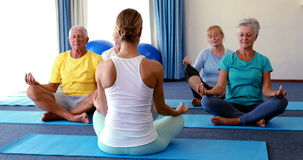 Trainer assisting senior citizens in practicing yoga. At home stock video footage