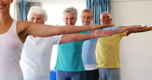 Trainer assisting senior citizens in practicing yoga. At home stock footage