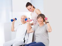 Trainer assisting senior couple with dumbbells Royalty Free Stock Image