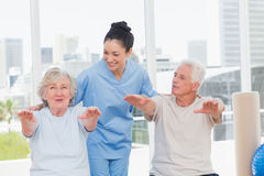 Trainer assisting senior couple to exercise Royalty Free Stock Images