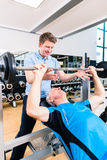 Trainer assisting senior man lifting barbell in gym Stock Images