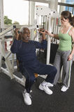 Trainer Assisting Senior Man Lifting Weights Stock Photography
