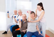 Trainer assisting senior people at healthclub Royalty Free Stock Photos