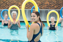 Trainer assisting senior swimmers with pool noodle. Happy trainer assisting senior swimmers with pool noodle Royalty Free Stock Photography