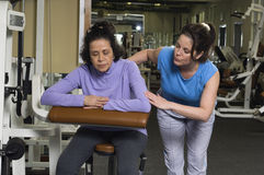 Trainer Assisting Senior Woman in Gymnastiek stock foto