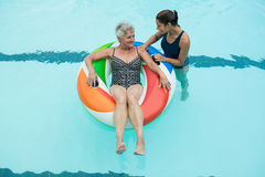 Trainer assisting senior woman on inflatable ring in swimming pool Stock Image