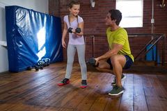 Trainer assisting teenage girl in exercise. At fitness studio Royalty Free Stock Images