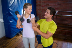 Trainer assisting teenage girl in exercise. At fitness studio Stock Images