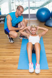 Trainer assisting woman with abdominal crunches at fitness studio Stock Image
