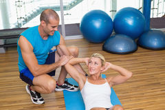 Trainer assisting woman with abdominal crunches at fitness studio. Male trainer assisting young women with abdominal crunches at fitness studio Royalty Free Stock Images