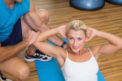 Trainer assisting woman with abdominal crunches at fitness studio. Male trainer assisting young women with abdominal crunches at fitness studio Stock Image