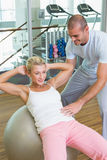 Trainer assisting woman with abdominal crunches at gym. Male trainer assisting women with abdominal crunches at the gym Royalty Free Stock Photo