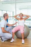 Trainer assisting woman with abdominal crunches at gym. Male trainer assisting women with abdominal crunches at the gym Royalty Free Stock Photography