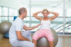 Trainer assisting woman with abdominal crunches at gym Royalty Free Stock Photography