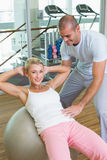 Trainer assisting woman with abdominal crunches at gym. Male trainer assisting women with abdominal crunches at the gym Stock Photography