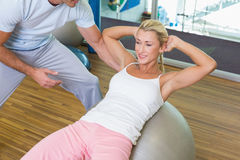Trainer assisting woman with abdominal crunches. Male trainer assisting women with abdominal crunches at the gym Royalty Free Stock Images