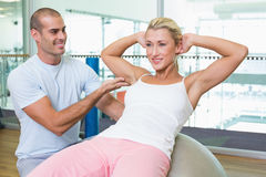 Trainer assisting woman with abdominal crunches. Smiling male trainer assisting women with abdominal crunches at the gym Stock Photos