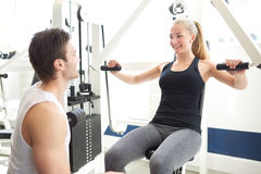 Trainer Assisting Woman on Chest Press Machine Royalty Free Stock Images