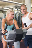 Trainer assisting woman with exercise bike at gym Stock Photography