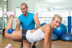 Trainer assisting woman with exercises at fitness studio. Side view of a male trainer assisting women with exercises at fitness studio Royalty Free Stock Photography