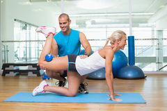 Trainer assisting woman with exercises at fitness studio. Side view of a male trainer assisting women with exercises at fitness studio Royalty Free Stock Photo